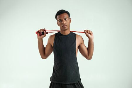 Ready for training. Strong and sporty young afro american man holding a jumping rope at his shoulders and looking at camera while standing against grey background