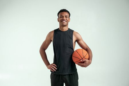 Cheerful player. Handsome young african man in sport clothing carrying a basketball ball and looking at camera with smile while standing against grey background Stock Photo