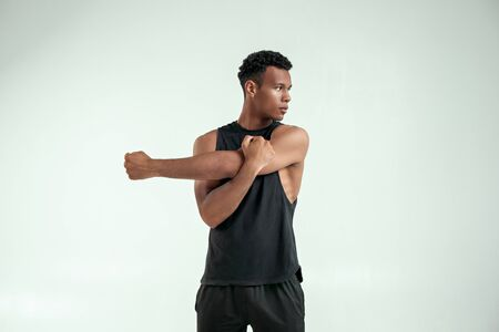 Important stretching. Strong young afro american man stretching his arm while standing against grey background