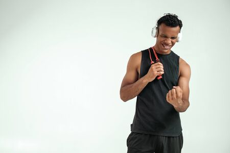 I can do everything. Cheerful young afro american man in headphones holding a jumping rope, smiling and clenching a fist while standing against grey background