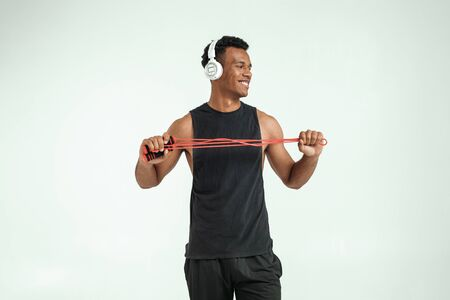 Exercising with music. Cheerful and sporty young afro american man in headphones holding a jumping rope and smiling while standing against grey background