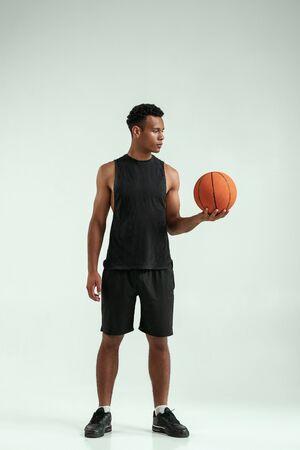 Pronto a giocare. A tutta lunghezza di un giovane africano fiducioso che porta una palla da basket e la guarda mentre si trova in studio su sfondo grigio
