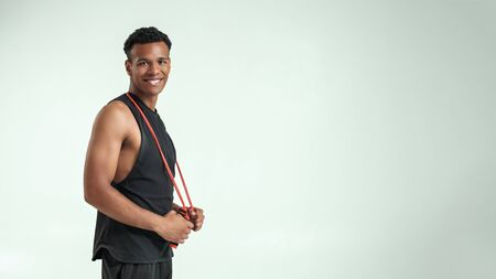 Feeling happy. Cheerful and young afro american man in sportswear holding a jumping rope at his shoulders and looking at camera with smile while standing against grey background Stock fotó