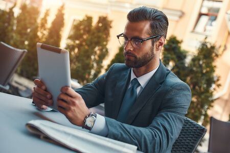 Modern businessman. Portrait of handsome bearded businessman in eyeglasses working with touchpad while sitting in restaurant outdoors 版權商用圖片
