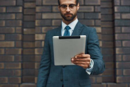 Modern businessman. Portrait of handsome bearded businessman in eyeglasses working with touchpad while standing against brick wall 版權商用圖片