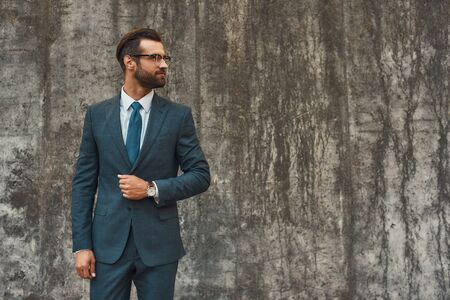 Great style. Confident bearded businessman in full suit looking away while standing against grey stone wall outdoors