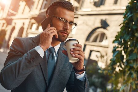 Important talk. Young and handsome bearded businessman in formal wear talking by phone with client and holding cup of coffee while standing outdoors 写真素材