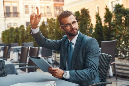 Portrait of handsome bearded businessman in eyeglasses holding touchpad and calling waiter while sitting in restaurant outdoors