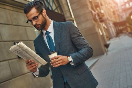 Young handsome bearded businessman in eyeglasses reading newspaper and holding cup of coffee while walking outdoors