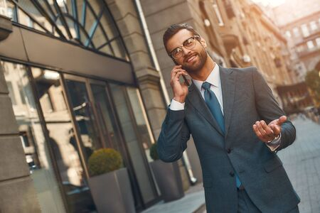 Happy to hear you Portrait of smiling bearded businessman in full suit talking by phone with client while walking outdoors Stockfoto