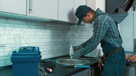 Working on it. Plumber installing sink siphon
