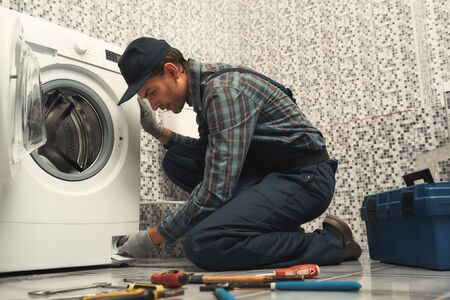 High quality workmanship. Plumber repairing washing machine