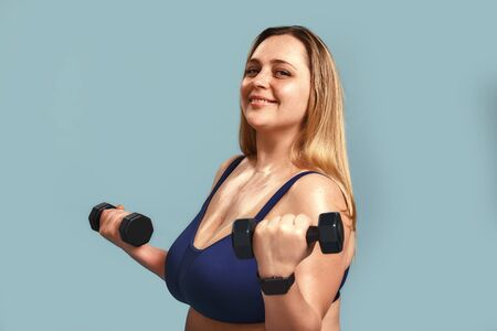 Happy to be healthy. Beautiful and positive plus size woman in sport clothes holding dumbbells and looking at camera with smile while standing inside against blue wall