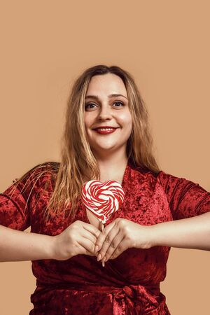 I love you. Plus size happy woman in velour dress holding a red heart-shaped lollipop and looking at camera with smile while standing in studio Фото со стока