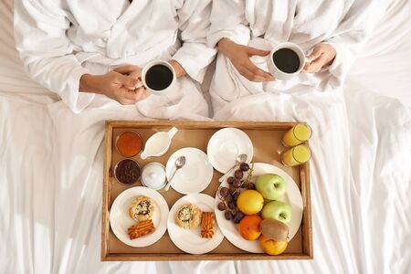 Everything. Right, where you need it. Couple relaxing in hotel room wearing robes Archivio Fotografico - 130297325
