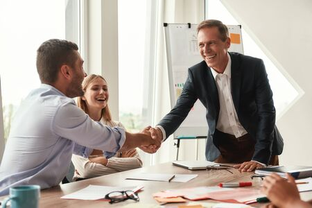 Welcome Two cheerful colleagues shaking hands and smiling while sitting in the modern office