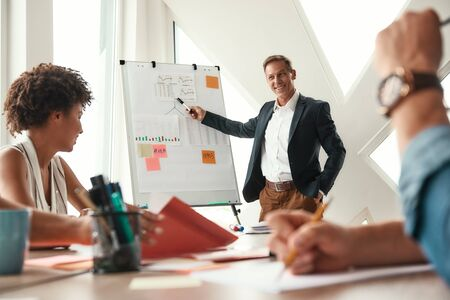 We have great results. Mature businessman standing near whiteboard and explaining something to his colleagues Stock Photo
