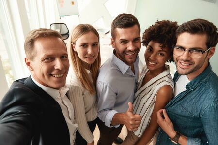 Group of cheerful colleagues taking selfie and gesturing while standing in the modern office Фото со стока