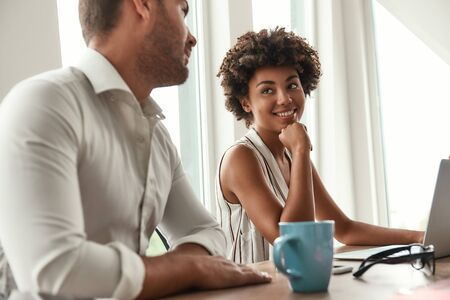 New working day. Young and beautiful afro american woman discussing something with her colleague while sitting in the modern office