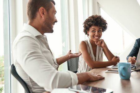 Sharing new ideas. Young man in white shirt discussing something with beautiful afro american woman while sitting at business meeting in the modern office