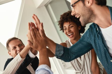 Celebrating success. Business people giving each other high-five and smiling while working together in the modern office