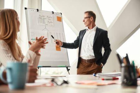 Regardez ici. Homme d'affaires mûr se tenant près du tableau blanc et expliquant quelque chose à son jeune collègue Banque d'images