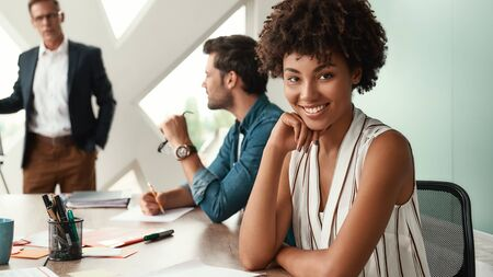 I am happy to work here! Young afro american woman is looking at camera and smiling while her boss standing near whiteboard and discussing something with team