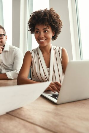 Great results! Young and beautiful afro american woman working on laptop and looking away with smile while sitting at the office table