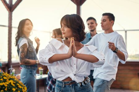 Feeling happy and peaceful. Pretty and young woman in white shirt is holding palms together while enjoying party on rooftop terrace with friends