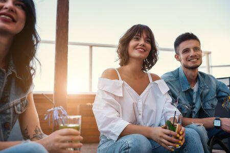 Gente feliz. Grupo de amigos bebiendo cócteles y pasando tiempo juntos sentados en el techo