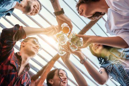 Spaß haben. Junge fröhliche Leute plaudern und trinken Cocktails, während sie auf dem Dach sitzen