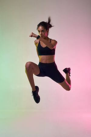 Never Stop Moving Full length of young athlete woman with perfect body in sports clothing jumping in studio against colorful background