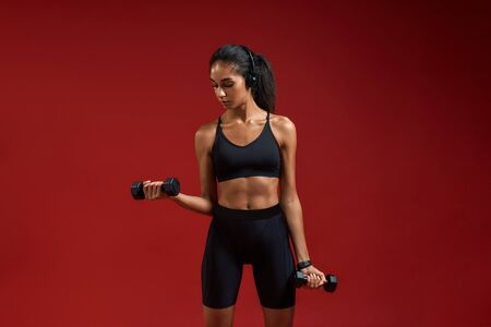 Good music for workout. Beautiful and sporty young woman in headphones exercising with dumbbells while standing against red background