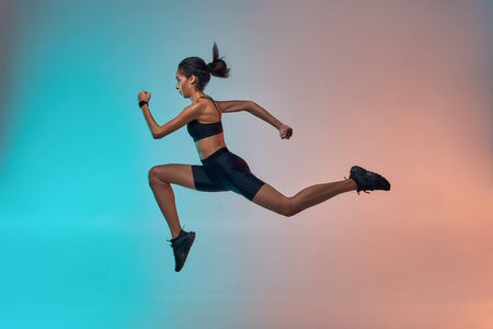 Never stop run Full length of young athlete woman with perfect body in sports clothing jumping in studio against colorful background Stock Photo