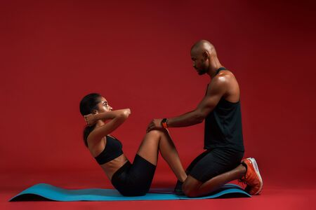 Abs exercises. Young and attractive woman lying on mat and doing sit ups with the assistance of a personal trainer