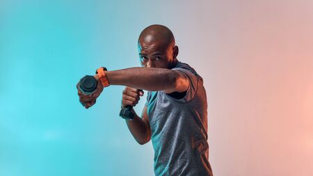 Perfect biceps. Muscular young african man exercising with dumbbells while standing against colorful background