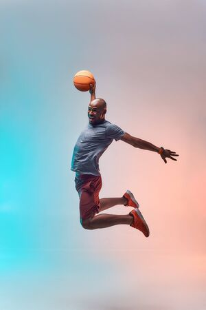 Basketball player in action. Full length of young african sportsman playing basketball and jumping against colorful background. Active lifestyle. Professional sport Reklamní fotografie