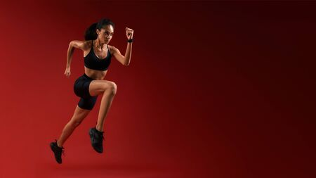 Higher and higher. Full length of young athlete woman in sports clothing jumping against red background