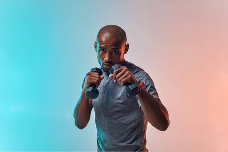Work hard! Muscular young african man exercising with dumbbells while standing against colorful background Reklamní fotografie