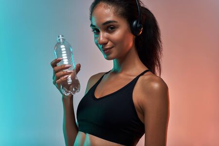 Profiter de la musique. Portrait d'une femme mignonne et sportive dans des écouteurs tenant une bouteille d'eau et regardant la caméra avec le sourire en se tenant debout sur un fond coloré Banque d'images
