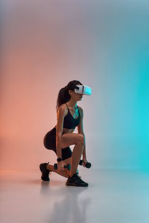 VR technology. Side view of young sporty woman in sports clothing exercising with dumbbells while wearing virtual reality glasses