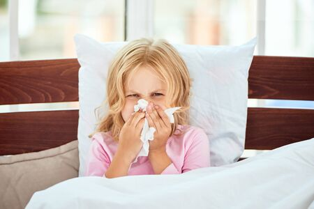 Catching a cold. Portrait of sick little girl with runny nose suffering from cold or flu while lying in bed at home