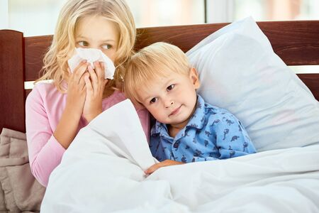 Just rest and sleep. Little sister and brother with runny noses suffering from flu or cold while lying in bed together at home. Virus disease