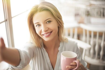 Young woman in cafe sitting with cup of coffee taking selfie photos on smartphone happy close-up