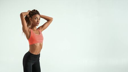 Perfect body. Side view of beautiful young african woman in sportswear holding her hair in hand while standing against grey background Imagens