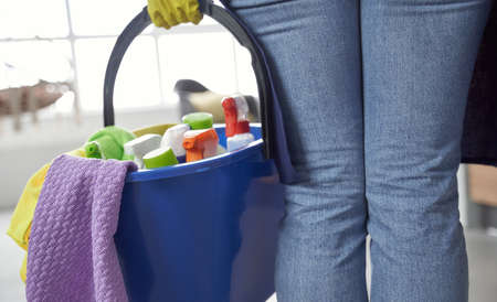 Cleaning products. Close up shot of woman holding plastic bucket or basket with rags, detergents and different cleaning supplies while cleaning at home Standard-Bild