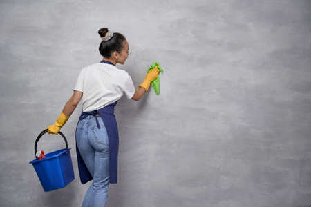 Full disinfection. Back view of housewife or maid woman uniform and yellow rubber gloves holding bucket with different cleaning products and cleaning grey wall