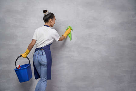 Back view of housewife or maid woman uniform and yellow rubber gloves holding bucket or basket with different cleaning products and cleaning a wall