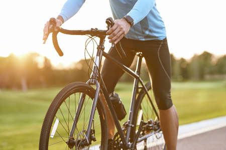 Cropped shot of professional road bicycle racer in sportswear cycling outdoors at sunset, man standing with bicycle on the road outdoors