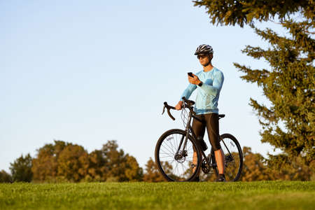 Young athletic man, professional cyclist in sportswear and protective helmet standing with his bike in park, using his smartphone and checking fitness results